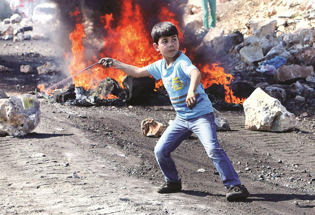 A Palestinian boy uses a sling to throw stones at Israeli soldiers during clashes at Kofr Qadom near Shechem on Friday. (REUTERS/Abed Omar Qusini)