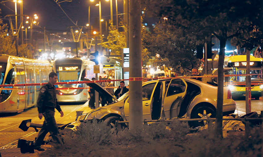 Police and rescue personnel at the scene where several people were injured when a car crashed into the Jerusalem light rail station. (Yonatan Sindel/Flash90)
