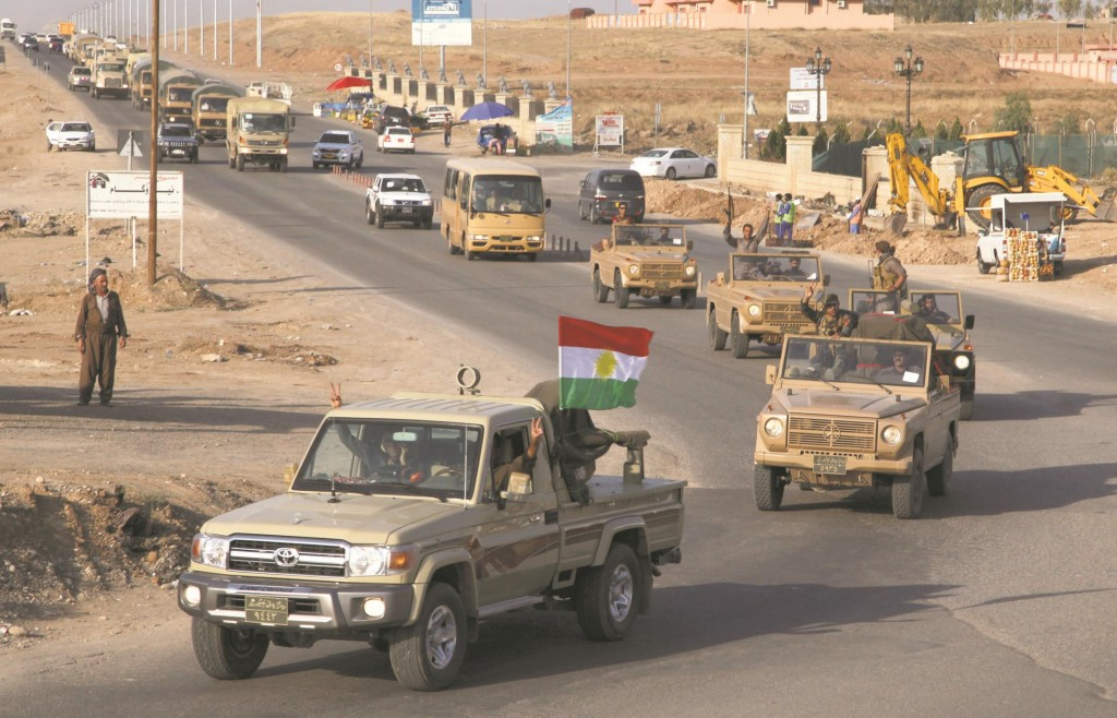 A convoy of Kurdish peshmerga fighters drive through Arbil after leaving a base in northern Iraq, on their way to the Syrian town of Kobani Tuesday. (REUTERS/Azad Lashkari)