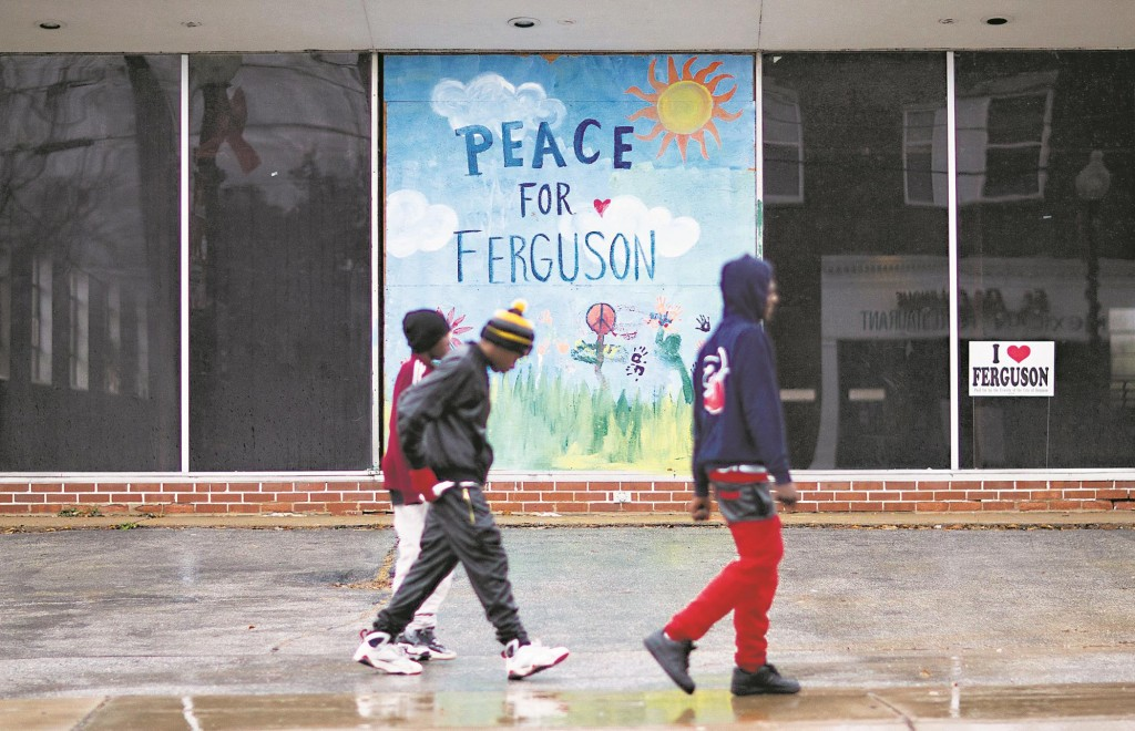 Youths walk past a mural depicting peace in Ferguson on a vacant building up the street from the city's police department, Sunday, in Ferguson, Mo.  (AP Photo/David Goldman)