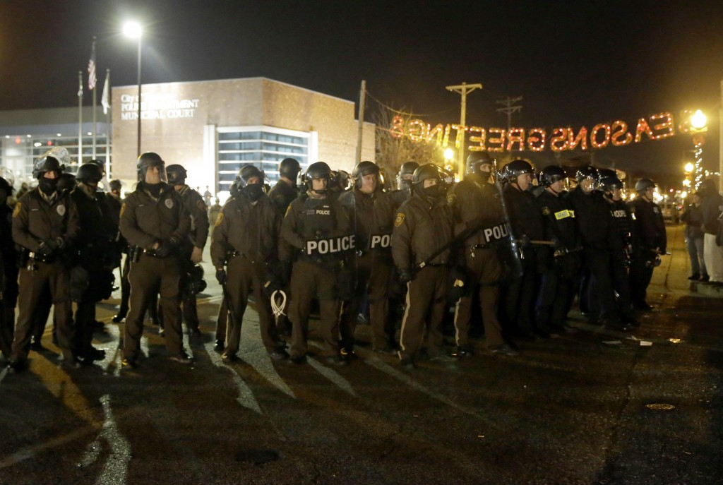 Police stand guard as protesters gather in front of Ferguson Police Department in Ferguson, Mo. (AP Photo/Jeff Roberson)