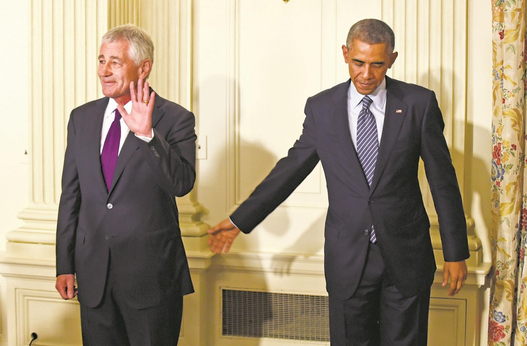 President Obama reaches over to Defense Secretary Chuck Hagel following an announcement of Hagel's resignation, Monday. (AP Photo/Susan Walsh)