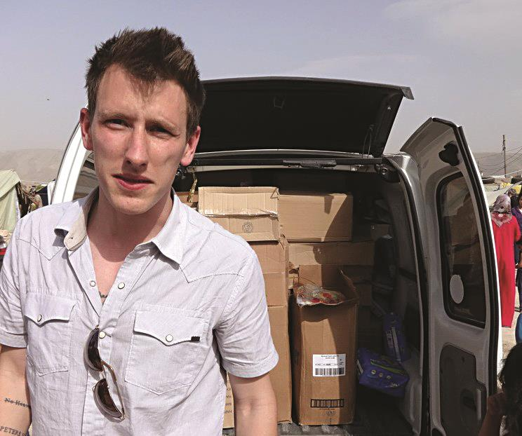 This undated file photo provided by the Kassig family shows Peter Kassig standing in front of a truck filled with supplies for Syrian refugees.  (AP Photo/Courtesy Kassig Family, File)