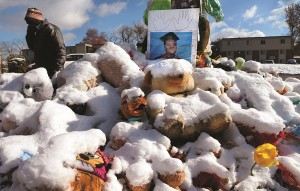 A high school graduation photo of Michael Brown rests on top of a snow-covered memorial, more than three months after the black teen was shot and killed nearby by a white policeman in Ferguson, Mo.  (AP Photo/St. Louis Post-Dispatch, Robert Cohen)
