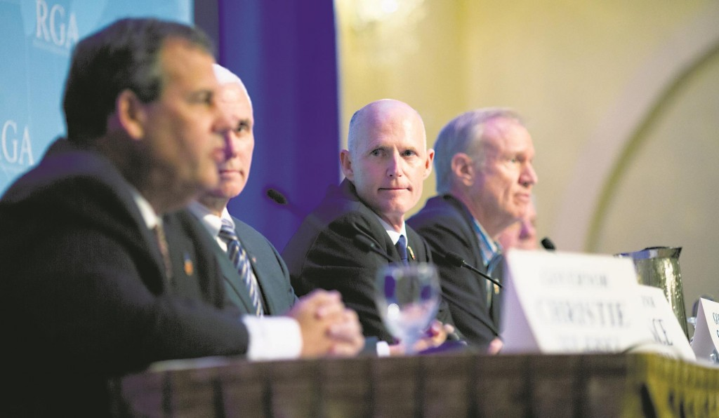Florida Gov. Rick Scott (C) listens as New Jersey Gov. Chris Christie (L) talks about immigration reform during a press conference at the Republican governors' conference in Boca Raton, Fla., Wednesday.  (AP Photo/J Pat Carter)