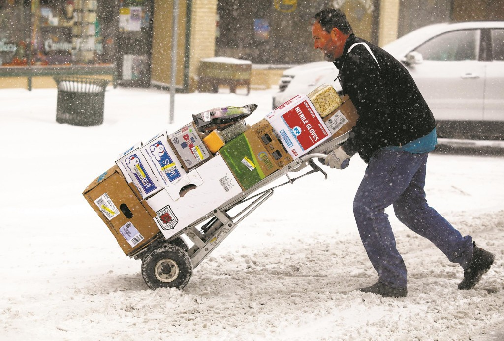 Paul Nettles pushes his cart through the snow while delivering food to restaurants Monday morning, in downtown Rapid City, S.D.  (AP Photo/Rapid City Journal, Chrfis Huber)