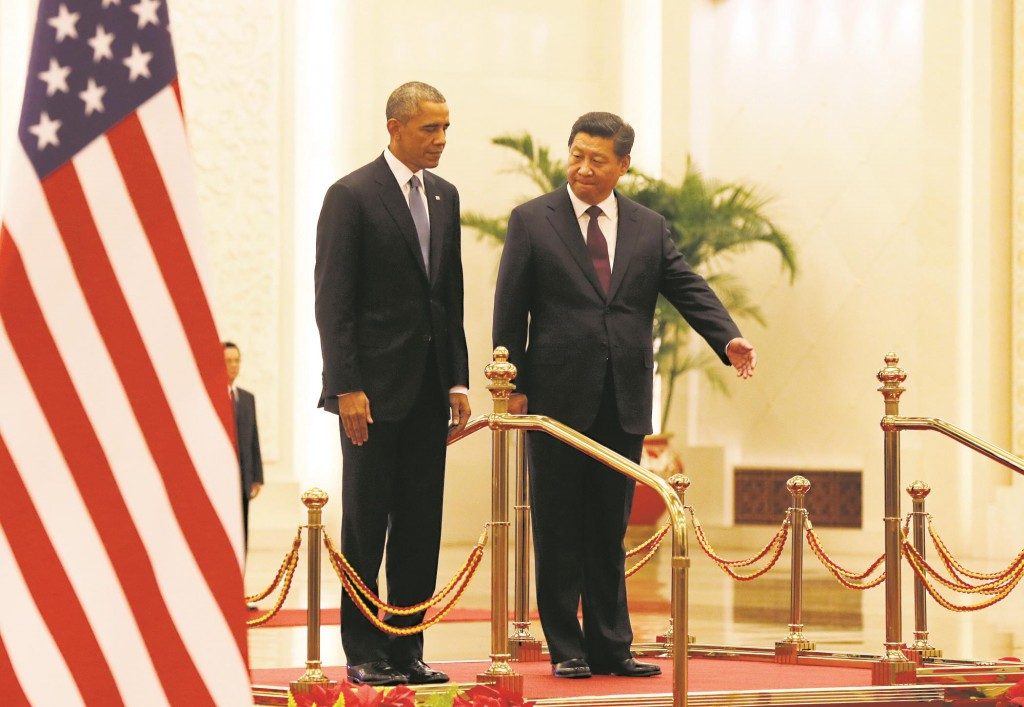 President Barack Obama (L) being shown the way by Chinese President Xi Jinping during a welcome ceremony at the Great Hall of the People in Beijing Wednesday. (AP Photo/Andy Wong)