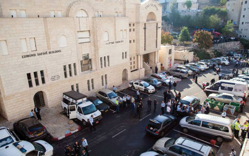 Police and rescue personnel at the scene after two terrorists from East Yerushalayim entered the Kehilas Bnei Torah shul in Har Nof, earlier this morning, with pistols and axes, killing four mispallelim. (Yonatan Sindel/Flash90)
