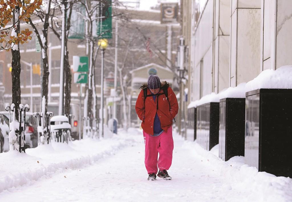 A pedestrian walks down a snow covered sidewalk Tuesday, in Kalamazoo, Mich. A November snow storm has dumped as much as a foot of snow in the Kalamazoo area.  (AP Photo/Kalamazoo Gazette-MLive Media Group, Mark Bugnaski)