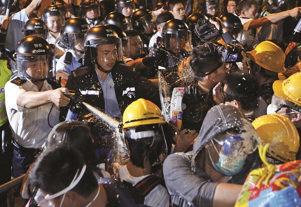 Police officers use pepper spray to stop pro-democracy protesters moving forward on the main road outside the government headquarters in Hong Kong on Sunday.  (AP Photo/Kin Cheung)