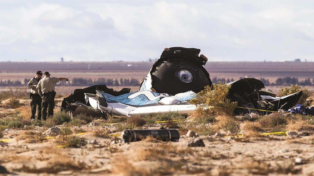 Law-enforcement officers take a closer look at the wreckage near the site where a Virgin Galactic space tourism rocket, SpaceShipTwo, exploded and crashed in Mojave, Calif.  (AP Photo/Ringo H.W. Chiu)