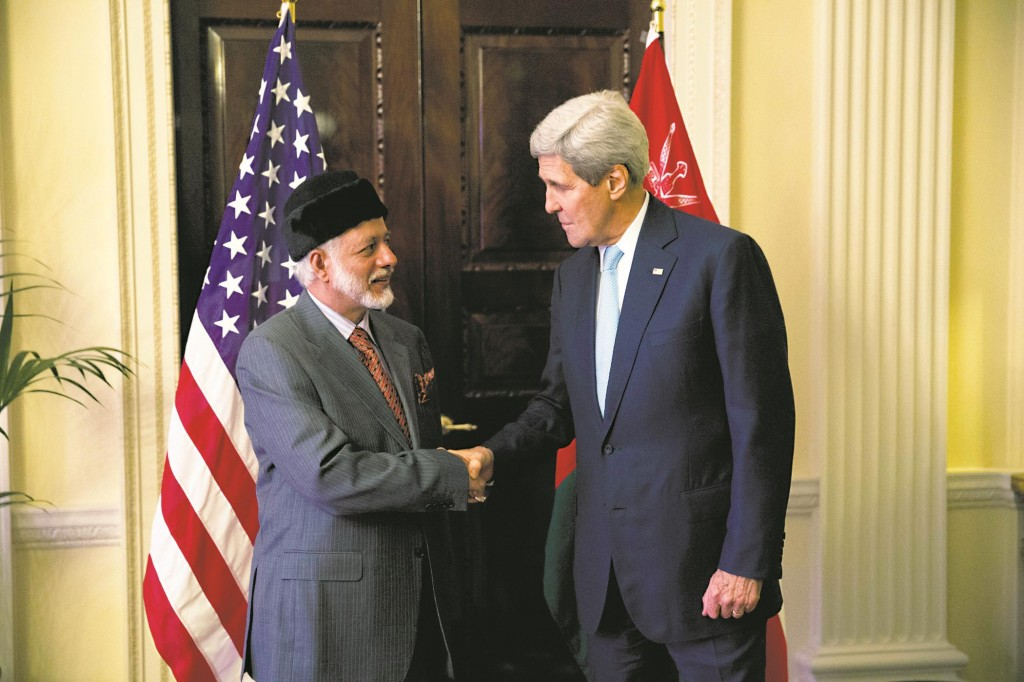 U.S. Secretary of State John Kerry (R) and Oman Foreign Minister Yusuf Bin Alawi bin Abdullah perform a posed handshake for photographers at the start of their meeting at the official residence of the U.S. ambassador to Britain, Winfield House, in London. (AP Photo/Matt Dunham)
