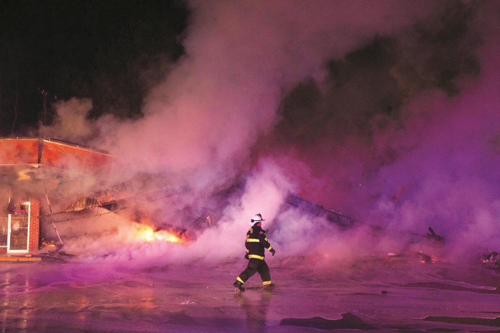 Firemen extinguish a burning business during rioting on November 25, 2014 in Dellwood, Missouri. Ferguson has been struggling to return to normal after Brown, an 18-year-old black man, was killed by Darren Wilson, a white Ferguson police officer, on August 9. His death has sparked months of sometimes violent protests in Ferguson. A grand jury declined to indict officer Wilson. (Aaron P. Bernstein/Getty Images)