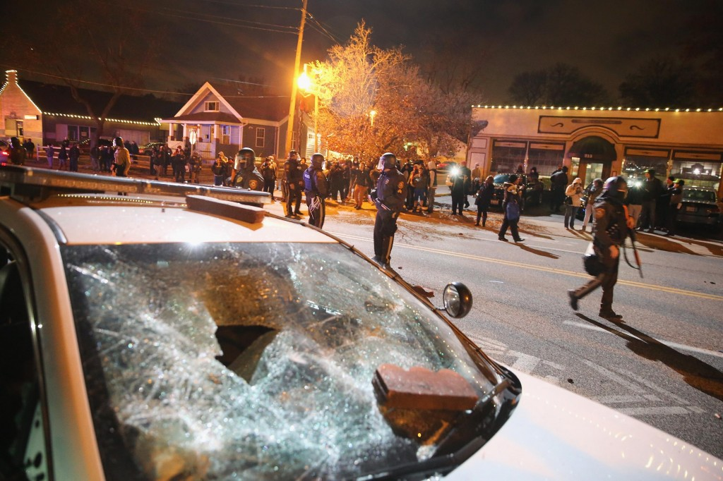 A damaged squad car sits nearby as police confront protestors after rioting broke out following the grand jury announcement in the Michael Brown case in Ferguson, Missouri. (Photo by Scott Olson/Getty Images)