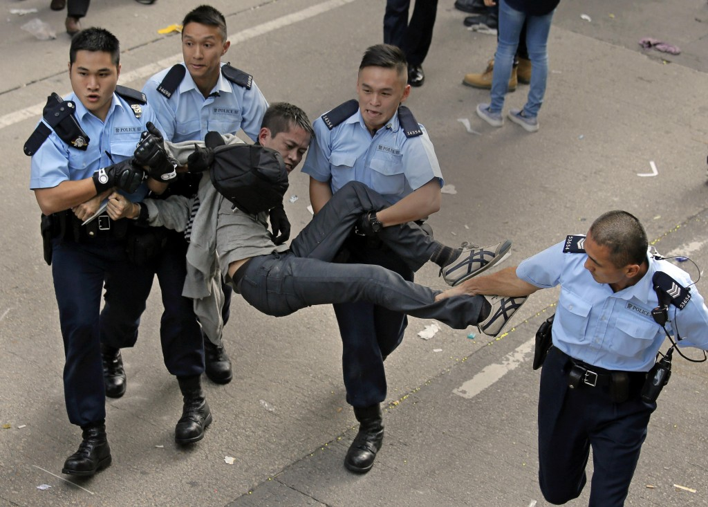 A pro-democracy protester is taken away by police officers as workers start clearing away barricades at an occupied area in Mong Kok district of Hong Kong Tuesday. (AP Photo/Vincent Yu)