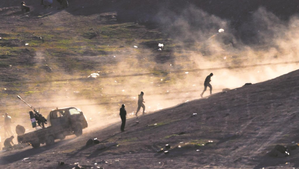Fighters run on a hillside after shooting a heavy machine gun toward the positions of the Islamic State on the outskirts of Kobani, as seen on the Turkish side of the Turkey-Syria border Tuesday. (AP Photo/Vadim Ghirda)