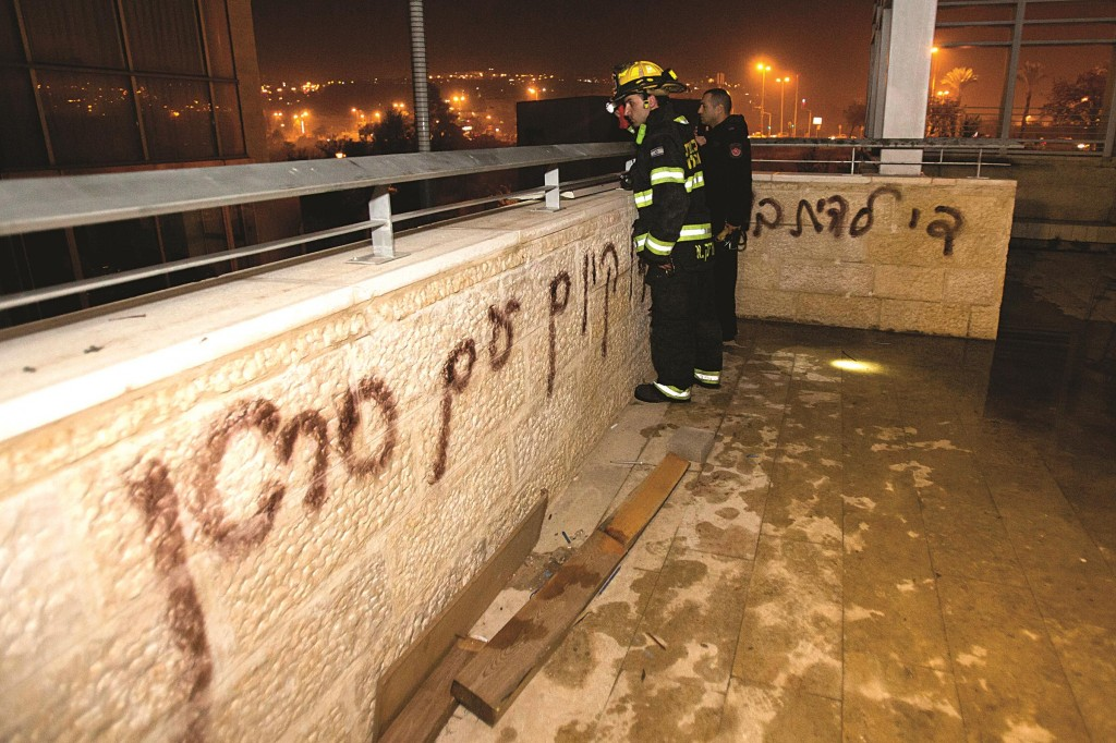 Firefighters and police at the scene where arsonists set fire to a classroom in a bilingual Hebrew-Arabic school in Jerusalem and wrote graffiti on the walls. (Yonatan Sindel/Flash90)