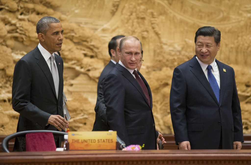 U.S. President Barack Obama, left, Chinese President Xi Jinping, right, and Russian President Vladimir Putin, center, arrive at the the Asia-Pacific Economic Cooperation (APEC) Summit plenary session at the International Convention Center, Yanqi, on Tuesday, Nov. 11, 2014 in Beijing. (AP Photo/Pablo Martinez Monsivais, Pool)