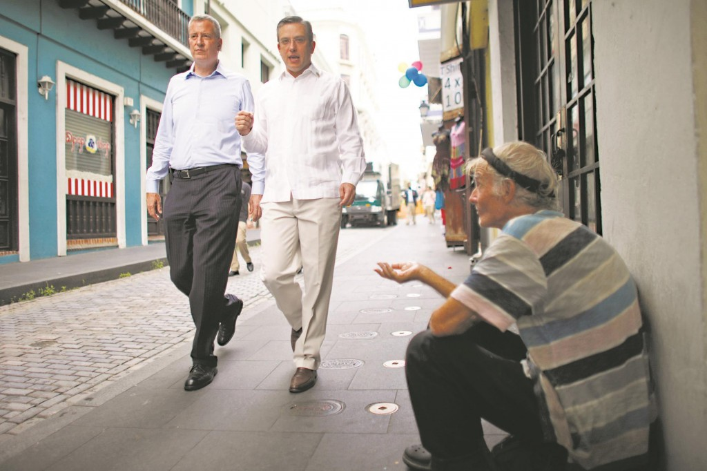 A beggar holds out his hand Saturday as Puerto Rico's Gov. Alejandro Garcia Padilla (R) and visiting Mayor Bill de Blasio take a stroll through the streets of Old San Juan. (AP Photo/Ricardo Arduengo)