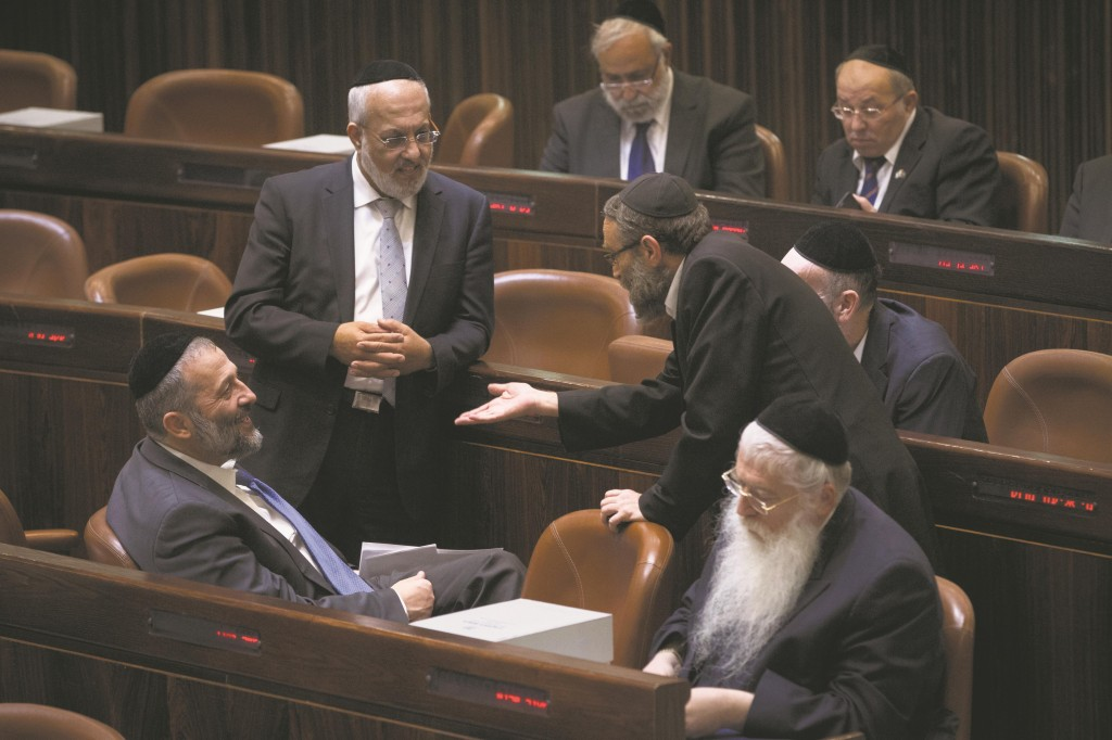 Leader of Shas Aryeh Deri (L) speaking with UTJ MK Rabbi Moshe Gafni in the Knesset plenum. (Miriam Alster/FLASH90)