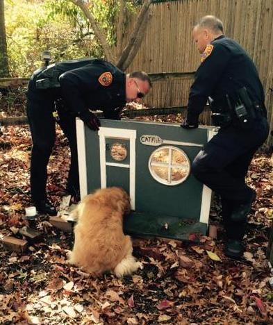 "Two police officers on Friday work to free a golden retriever named ""Buddy"" who got his head caught in the entrance of a cat's house. (AP Photo/Suffolk County Police Department)"