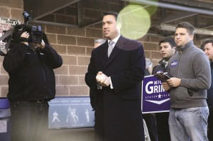 Rep. Michael Grimm on Monday waits to greet people as they exit a grocery store in Staten Island. (AP Photo/Seth Wenig)