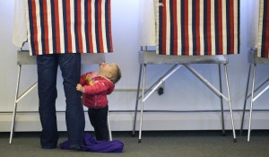 A child looks up at a voter Tuesday at the Alaska Zoo polling place in Anchorage, Alaska. (AP Photo/Ted S. Warren)