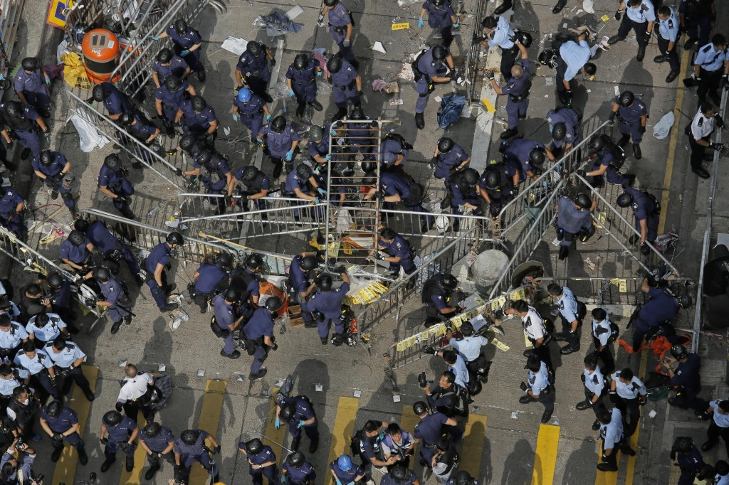 Police officers clear metal barricades, while others (not shown) tear down protesters' tents and canopies and carry away other obstructions in the Mong Kok district of Hong Kong, Thursday.  (AP Photo/Vincent Yu)
