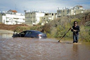 A man tries to pull his car out of the flooding in Or Yehudah, central Israel, after heavy rain on Sunday. (FLASH90)