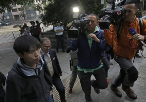 Prominent Hong Kong student protest leader Joshua Wong, center, walks out from a court with his lawyer in Hong Kong Thursday, Nov. 27.  (AP Photo/Vincent Yu)