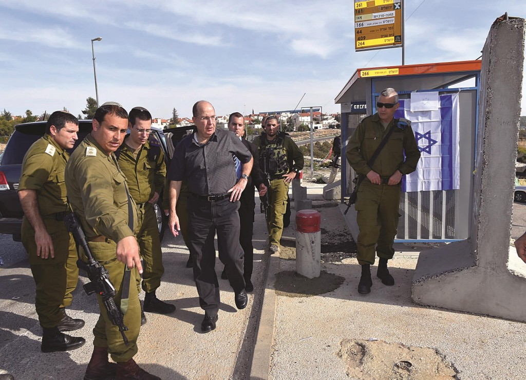 Defense Minister Moshe Yaalon visits the bus stop where a stabbing attack took place on Monday at the entrance to Alon Shvut. (Ariel Hermoni/Ministry of Defense)