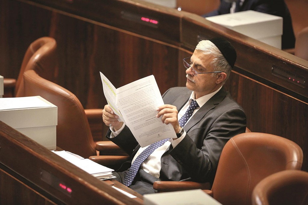 Member of Knesset Amnon Cohen (Shas) looking over the new budget in the plenum on Monday. (Hadas Parush/Flash90)