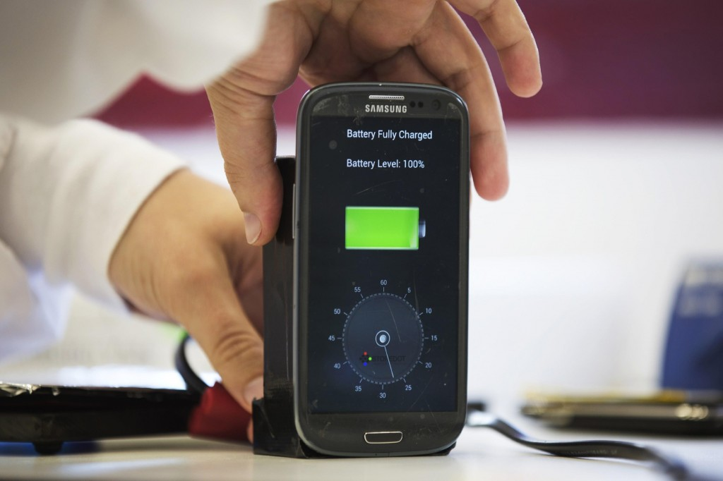 A lab worker disconnects a mobile phone from a charger, displaying a timer indicating that the battery was fully charged under 30 seconds, at the headquarters of StoreDot in Tel Aviv on Monday. (Caption REUTERS/Finbarr O'Reilly)
