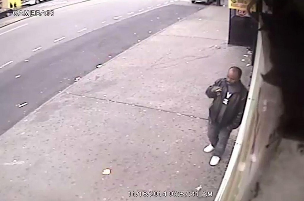A man suspected of shoving a stranger in front of an oncoming train smokes a cigarette outside a convenience store in the Bronx hours afterward. (AP Photo/NYPD)