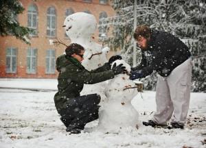 Two Clarkson University students build a snowman on Monday. (AP Photo/The Buffalo News, Derek Gee)