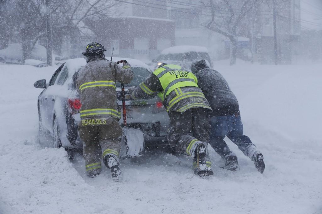 Firefighters on Tuesday help a motorist on the Thruway. (AP Photo/The Buffalo News, Derek Gee)