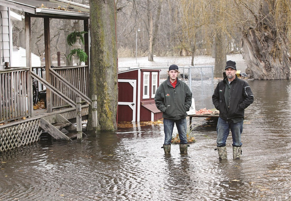 Gregory Sojka, right, and his son Jake stand Tuesday alongside their flooded home in Bowmansville, N.Y., after Ellicott Creek crested its banks. (AP Photo/Gary Wiepert)