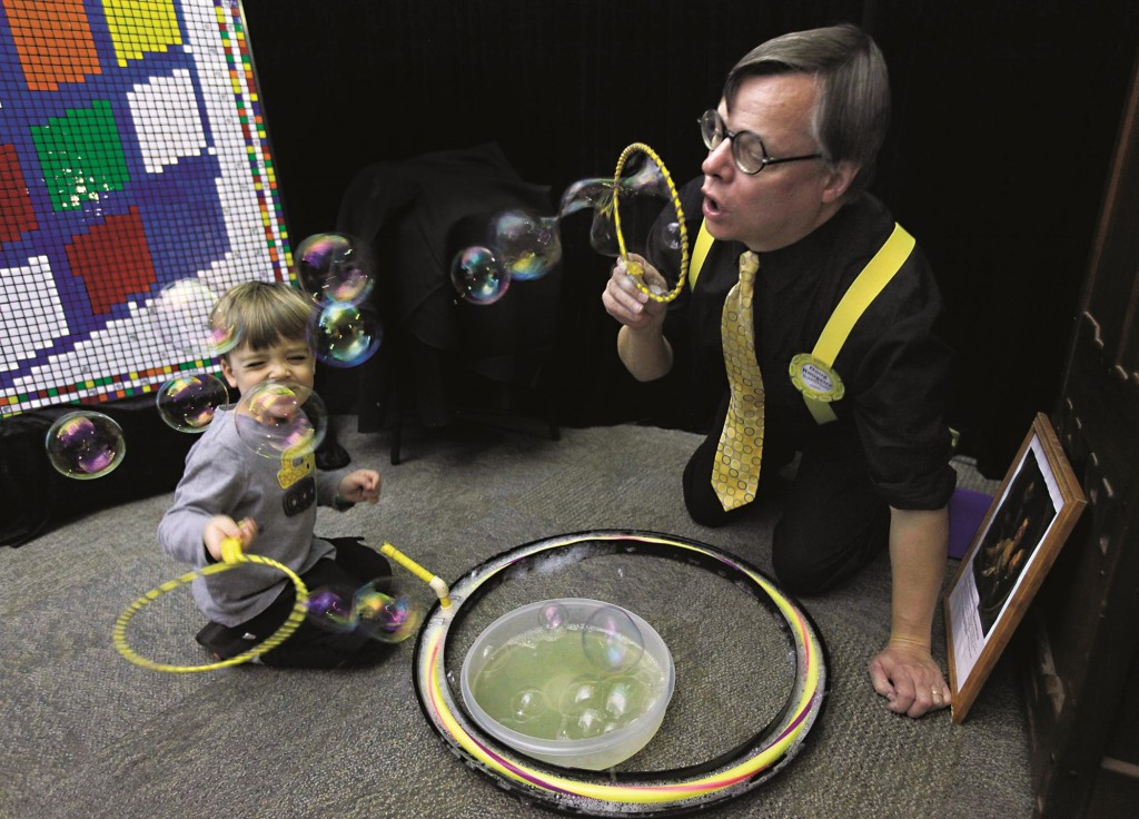 Tyler DuPont, 3, is amused by bubbles expert Doug Rougeux at the National Toy Hall of Fame in Rochester, N.Y. (AP Photo/Democrat & Chronicle, Carlos Ortiz)