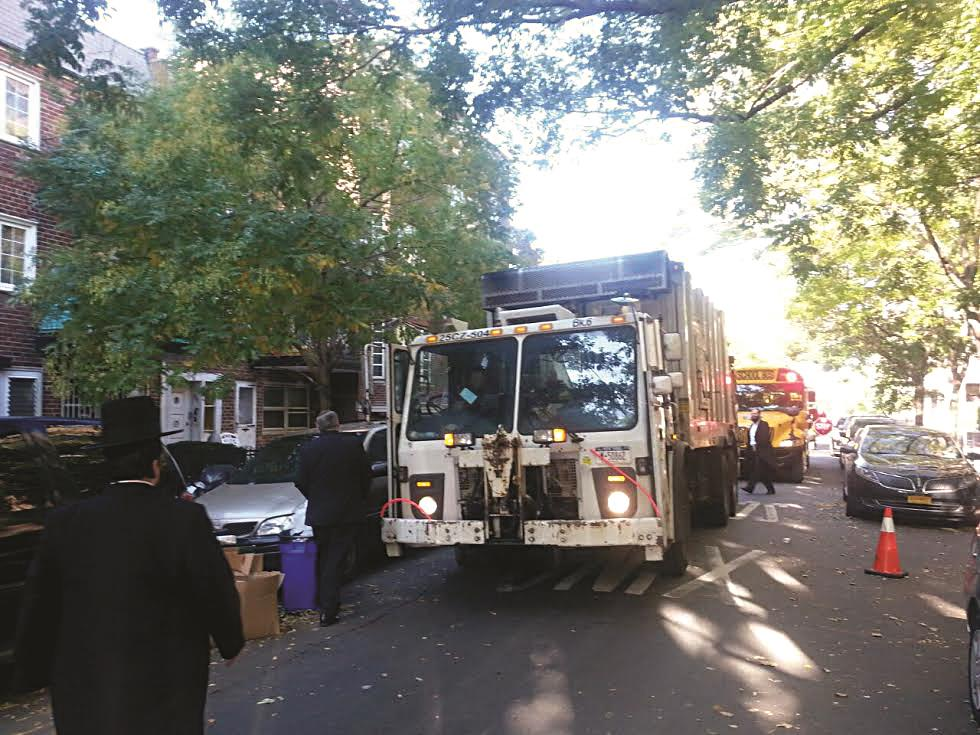 Assemblyman Dov Hikind (left of garbage truck) on Monday morning going to speak with sanitation truck drivers who were blocking school buses in Boro Park.