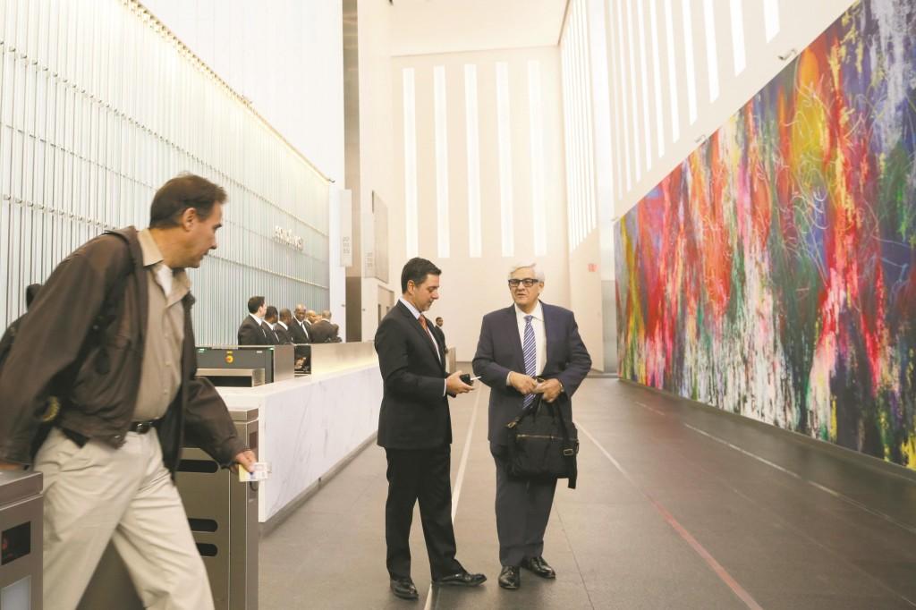 A Conde Nast employee on Monday enters the lobby of 1 World Trade Center. (AP Photo/Mark Lennihan)