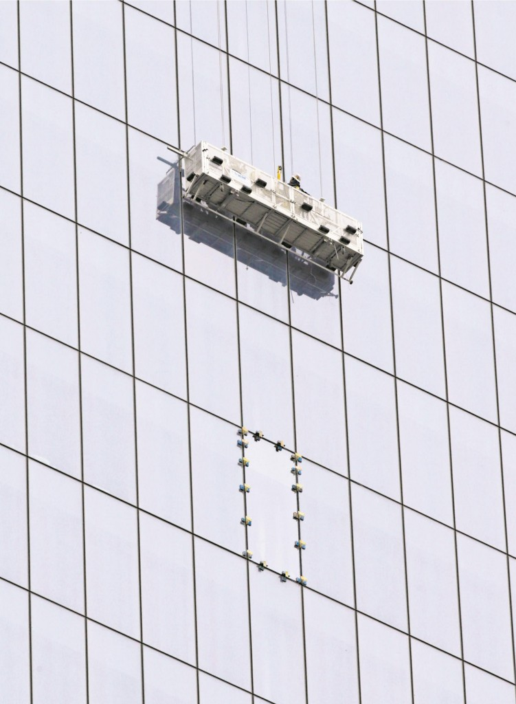 Workers raise their scaffold Thursday after replacing a pane at 1 World Trade Center that was cut to save the window washers. (AP Photo/Kathy Willens)