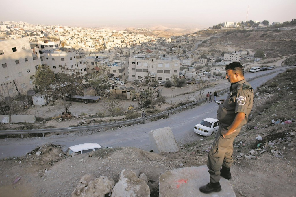 An Israeli policeman stands looking over the flashpoint Arab village of Issawiya. (AHMAD GHARABLI/AFP/Getty Images)