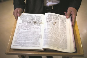 "A man holds a Gemara with bullet holes found inside the Kehilas Yaakov shul in Har Nof, Yerushalayim, after Arab terrorists armed with pistols and axes murdered four mispallelim wearing tallis and tefillin and wounded five others, including an Israeli Druze police officer who later succumbed to his wounds in Hadassah Hospital.  The photo of the scarred Gemara brings to mind the story of Harav Avraham Weinberg, Hy""d, (1872–1942), a member of the Vaad Harabbanim in the Warsaw Ghetto. Despite the oppressive conditions in the ghetto, Harav Weinberg persisted in delivering a regular shiur in his home until the Germans conducted a brutal aktion on his street. He and his students were literally dragged from their studies and deported to Treblinka. The Gemaras they used were left open on the table. (Dr. Hillel Zeidman — Warsaw Ghetto Diary/Witness to History)  (Noam Revkin Fenton/Flash90)"