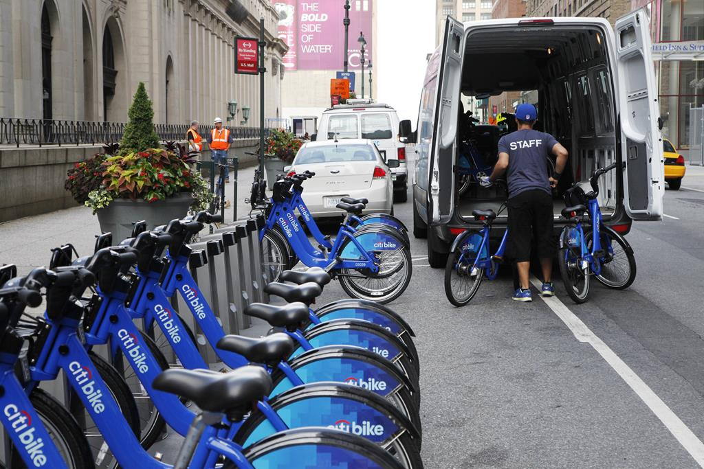 A Citi Bike employee loads bikes into a van to move them to another New York location, midtown Manhattan.  (AP Photo/Mark Lennihan)