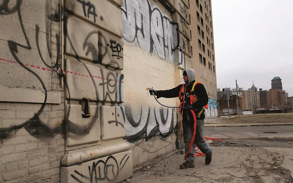 Laborer Brian Kuhn paints over graffiti on a blighted building near downtown Detroit in Detroit, Michigan, Wednesday as Detroit was about to emerge from Bankruptcy.  (REUTERS/Rebecca Cook)