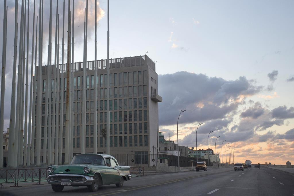 An American classic car passes next to the building of the U.S. Interests Section in Havana, Cuba, Wednesday. President Barack Obama announced the re-establishment of diplomatic relations as well as an easing in economic and travel restrictions on Cuba Wednesday. (AP Photo/Desmond Boylan)