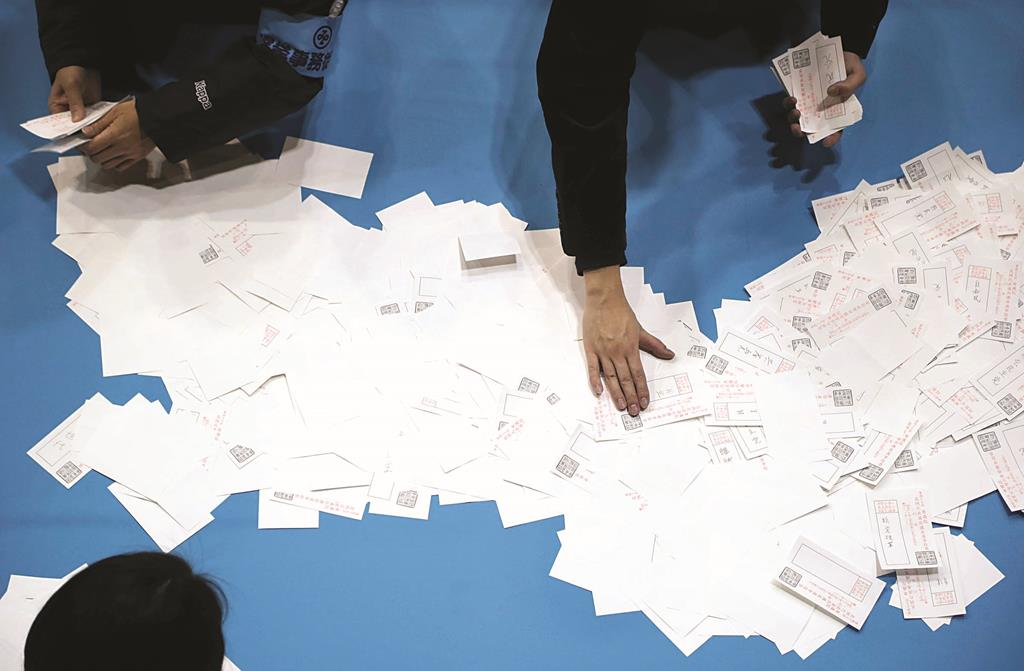 Election staff members count votes in lower house elections at a ballot counting center in Tokyo on Sunday. (AP Photo/Koji Sasahara)
