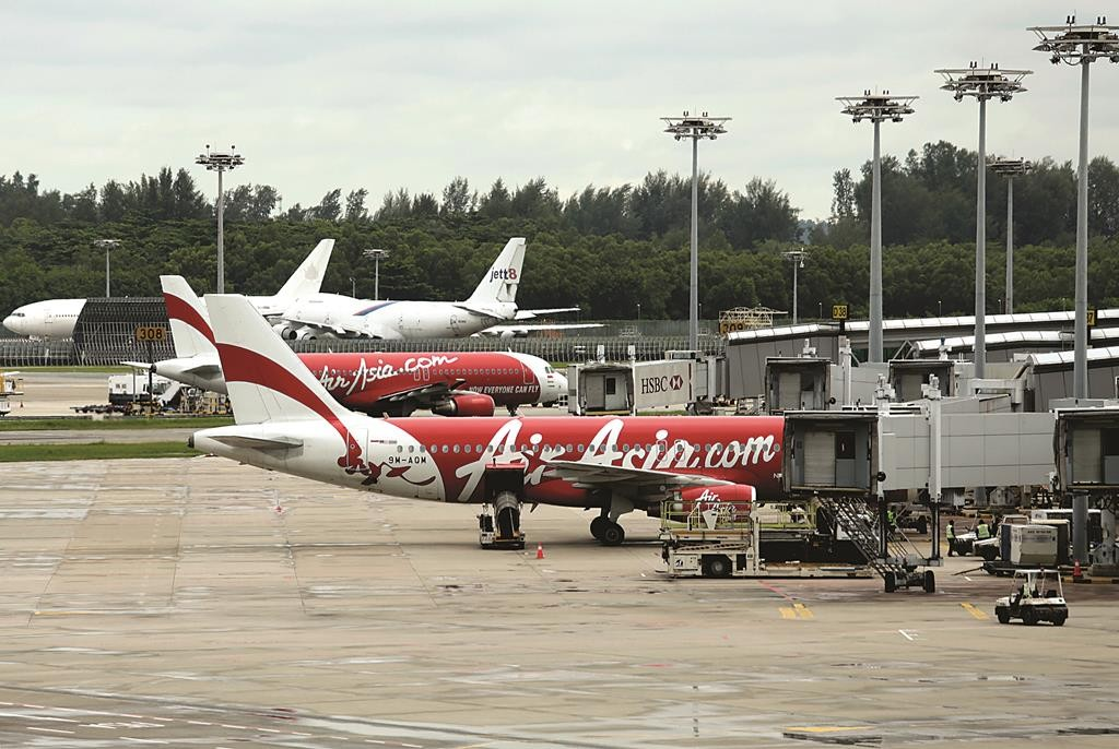 An AirAsia plane taxis, while another is parked on the tarmac at the Changi International Airport on Monday in Singapore. (AP Photo/Wong Maye-E)