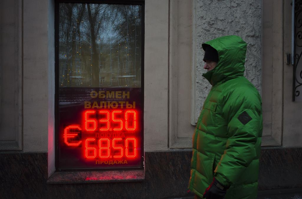 A man walks along the Boulevard Ring in downtown Moscow, Russia, Wednesday, with a currency exchange office sign in a window.  (AP Photo/Alexander Zemlianichenko)
