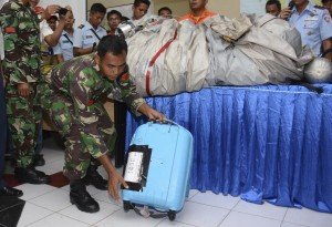 A member of the Indonesian Air Force shows a suitcase and airplane parts (on the table) recovered from the water near the site where AirAsia Flight 8501 disappeared, during a press conference at the airbase in Pangkalan Bun, Central Borneo, Indonesia, Tuesday. (AP Photo/Dewi Nurcahyani)